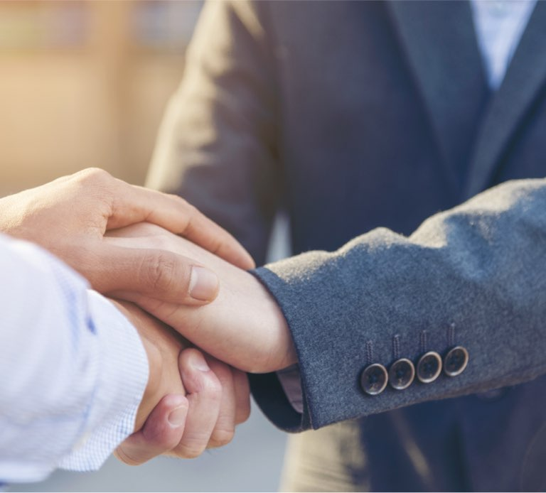 Man shaking another man's hand showing absolute trust